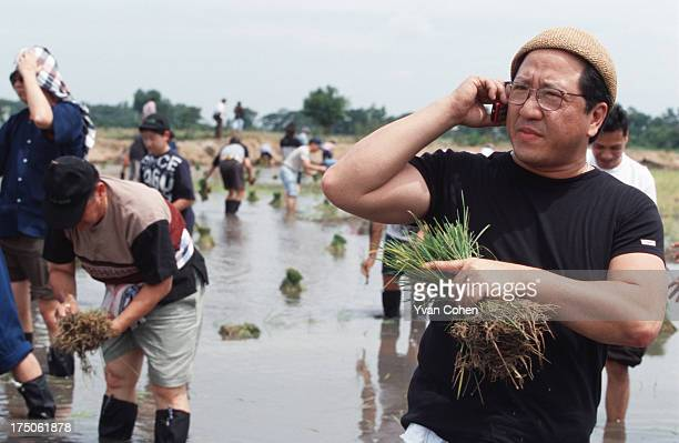 Khun Boonchai Bencharongkul managing director of DTAC mobile phone company during a rice planting excursion on his land in Saraburi province a couple...