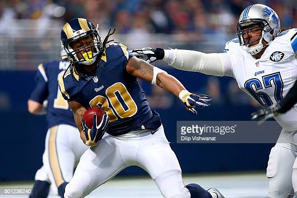 Khyri Thornton of the Detroit Lions reaches for Todd Gurley of the St Louis Rams as he carries the ball in the second quarter at the Edward Jones...