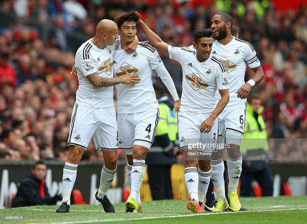 Ki SungYeung of Swansea City celebrates scoring the opening goal with his teammates during the Barclays Premier League match between Manchester...