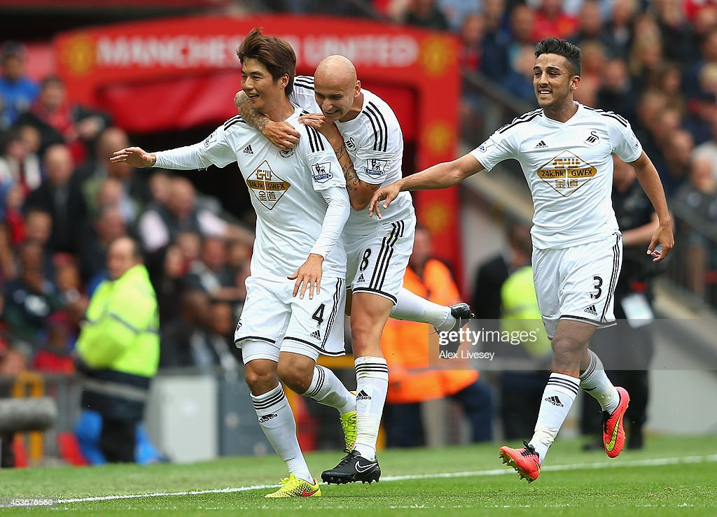 Ki Sung-Yeung of Swansea City celebrates scoring the opening goal with his team-mates <a gi-track='captionPersonalityLinkClicked' href=/galleries/search?phrase=Jonjo+Shelvey&family=editorial&specificpeople=4940315 ng-click='$event.stopPropagation()'>Jonjo Shelvey</a> and Neil Taylor (R) during the Barclays Premier League match between Manchester United and Swansea City at Old Trafford on August 16, 2014 in Manchester, England.