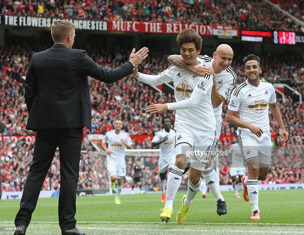 Ki Sung-Yeung of Swansea City celebratres scoring their first goal with manager Garry Monk (l) during the Premier League match between Manchester United and Swansea City at Old Trafford on August 16, 2014 in Manchester, England.