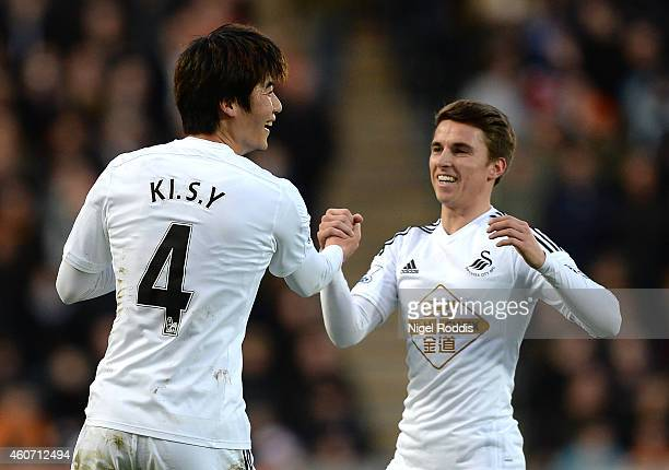 Ki SungYueng of Swansea City celebrates scoring the opening goal with teammate Tom Carroll during the Barclays Premier League match between Hull City...
