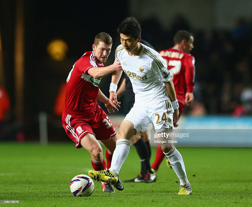 Ki Sung-Yueng (R) of Swansea City challenged by Richard Smallwood (L) of Middlesbrough during the Capital One Cup Quarter-Final match between Swansea City and Middlesbrough at the Liberty Stadium on December 12, 2012 in Swansea, Wales.