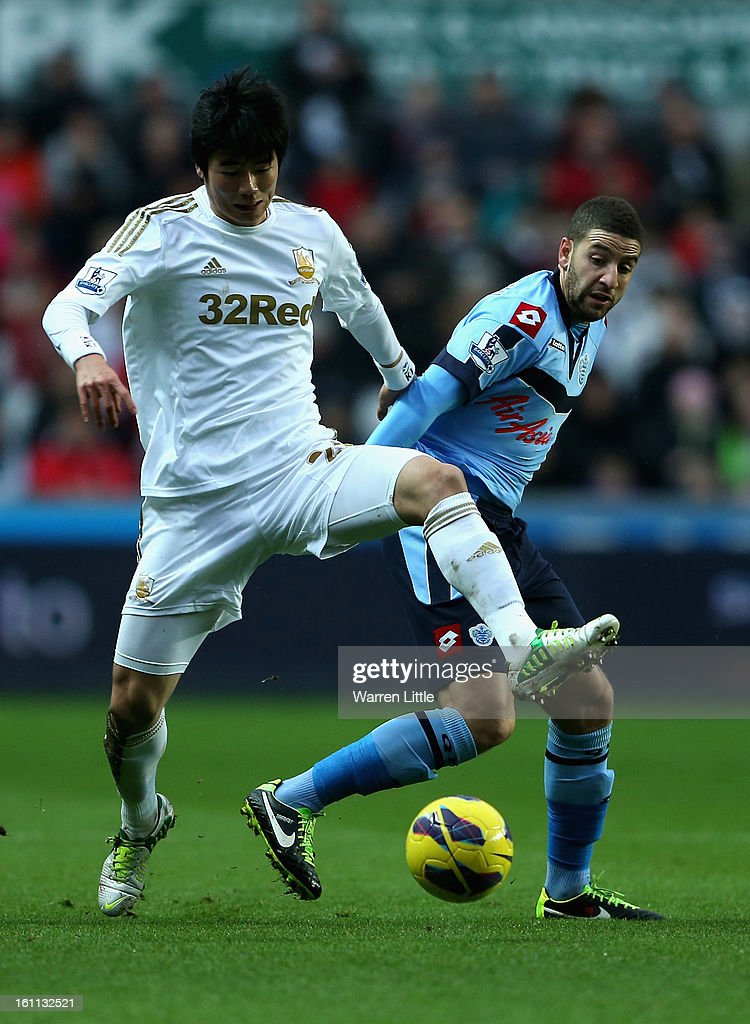 Ki Sung-Yueng of Swansea City is tackled by Adel Taarabt of Queens Park Rangers during the Premier League match between Swansea City and Queens Park Rangers at Liberty Stadium on February 9, 2013 in Swansea, Wales.