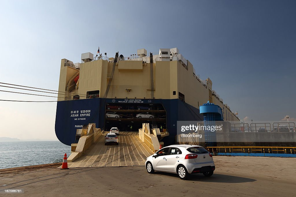 Kia Motors Corp. vehicles bound for export are driven into a Eukor Car Carriers Inc. roll-on/roll-off (RORO) cargo ship at the port of Pyeongtaek in Pyeongtaek, South Korea, on Monday, Sept. 30, 2013. South Koreas consumer confidence sank to a five-month low in September, even after a rebound in exports fueled the fastest economic growth in two years last quarter. Photographer: SeongJoon Cho/Bloomberg via Getty Images