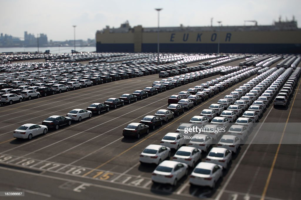 Kia Motors Corp. vehicles bound for export await shipment in front of a Eukor Car Carriers Inc. roll-on/roll-off (RORO) cargo ship in this photograph taken with a tilt-shift lens at the port of Pyeongtaek in Pyeongtaek, South Korea, on Monday, Sept. 30, 2013. South Koreas consumer confidence sank to a five-month low in September, even after a rebound in exports fueled the fastest economic growth in two years last quarter. Photographer: SeongJoon Cho/Bloomberg via Getty Images