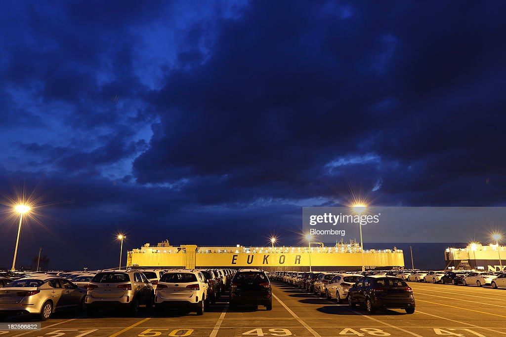 Kia Motors Corp. vehicles bound for export await shipment in front of a Eukor Car Carriers Inc. roll-on/roll-off (RORO) cargo ship at dusk at the port of Pyeongtaek in Pyeongtaek, South Korea, on Monday, Sept. 30, 2013. South Koreas consumer confidence sank to a five-month low in September, even after a rebound in exports fueled the fastest economic growth in two years last quarter. Photographer: SeongJoon Cho/Bloomberg via Getty Images