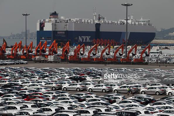 Kia Motors Corp vehicles bound for export await shipment in front of a Nippon Yusen Kaisha rollon/rolloff cargo ship at the port of Pyeongtaek in...