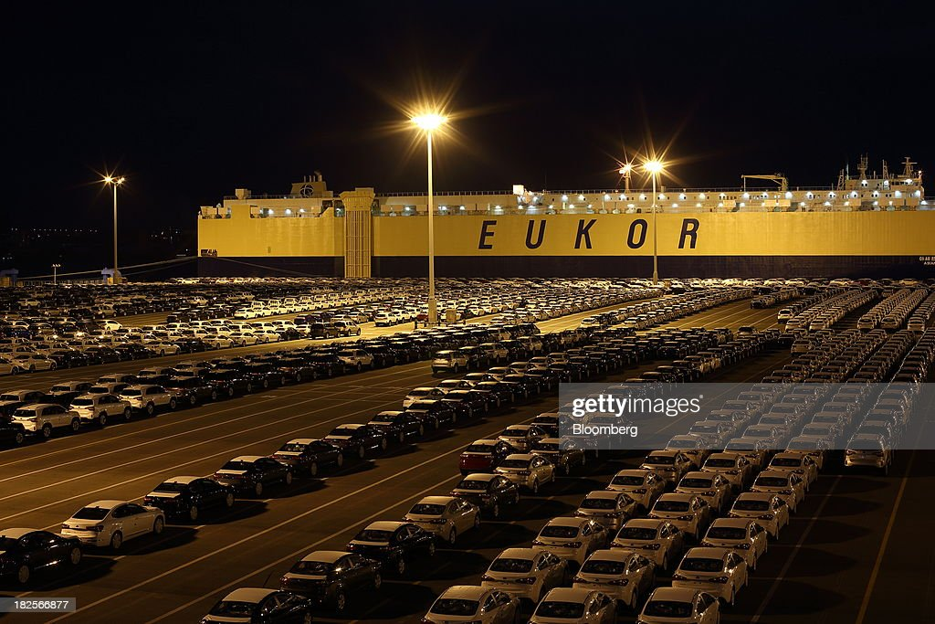 Kia Motors Corp. vehicles bound for export await shipment in front of a Eukor Car Carriers Inc. roll-on/roll-off (RORO) cargo ship at night at the port of Pyeongtaek in Pyeongtaek, South Korea, on Monday, Sept. 30, 2013. South Koreas consumer confidence sank to a five-month low in September, even after a rebound in exports fueled the fastest economic growth in two years last quarter. Photographer: SeongJoon Cho/Bloomberg via Getty Images