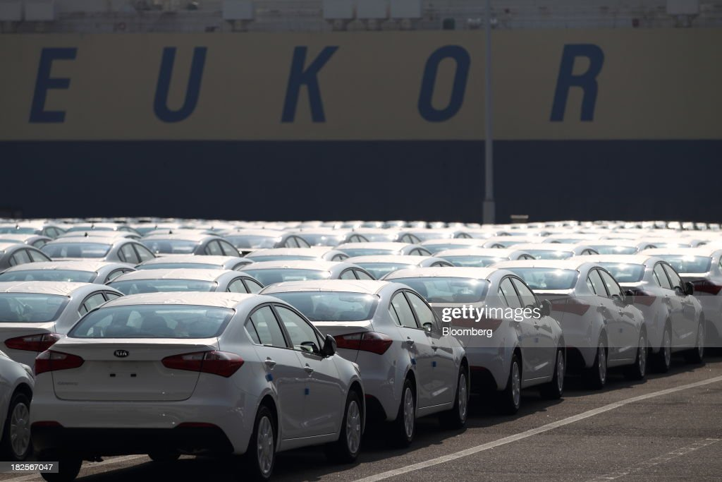Kia Motors Corp. vehicles bound for export await shipment in front of a Eukor Car Carriers Inc. roll-on/roll-off (RORO) cargo ship at the port of Pyeongtaek in Pyeongtaek, South Korea, on Monday, Sept. 30, 2013. South Koreas consumer confidence sank to a five-month low in September, even after a rebound in exports fueled the fastest economic growth in two years last quarter. Photographer: SeongJoon Cho/Bloomberg via Getty Images