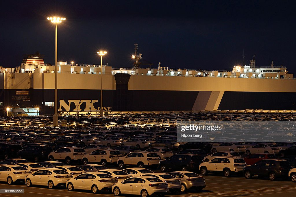 Kia Motors Corp. vehicles bound for export await shipment in front of a Nippon Yusen Kaisha (NYK Line) roll-on/roll-off (RORO) cargo ship at night at the port of Pyeongtaek in Pyeongtaek, South Korea, on Monday, Sept. 30, 2013. South Koreas consumer confidence sank to a five-month low in September, even after a rebound in exports fueled the fastest economic growth in two years last quarter. Photographer: SeongJoon Cho/Bloomberg via Getty Images