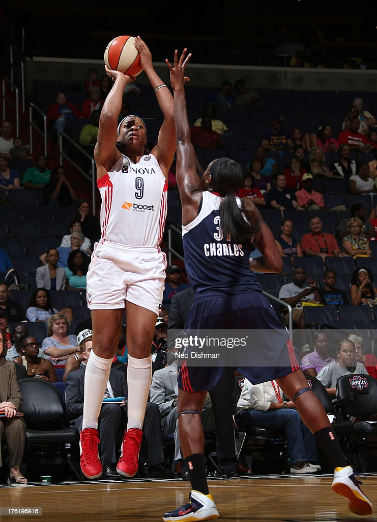 Kia Vaughn of the Washington Mystics shoots against Tina Charles of the Connecticut Sun at the Verizon Center on August 11 2013 in Washington DC NOTE...