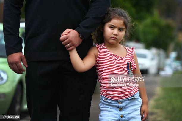 Kiarrah holds the hand of her father Australian Navy AB Seaman Murray Hall during a ANZAC service in Redern on April 25 2017 in Sydney Australia The...