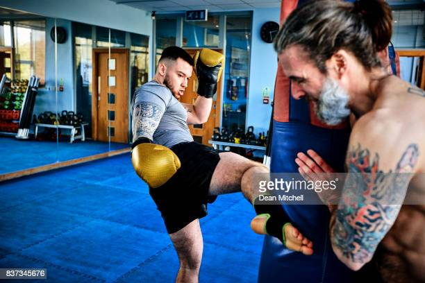 kick boxer striking a punching bag at gym