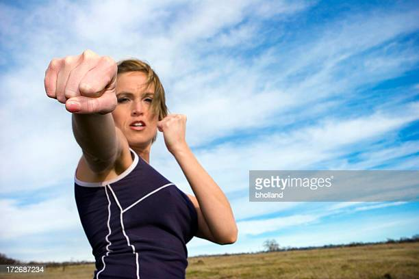 Kickboxing girl forward punching while standing in a field