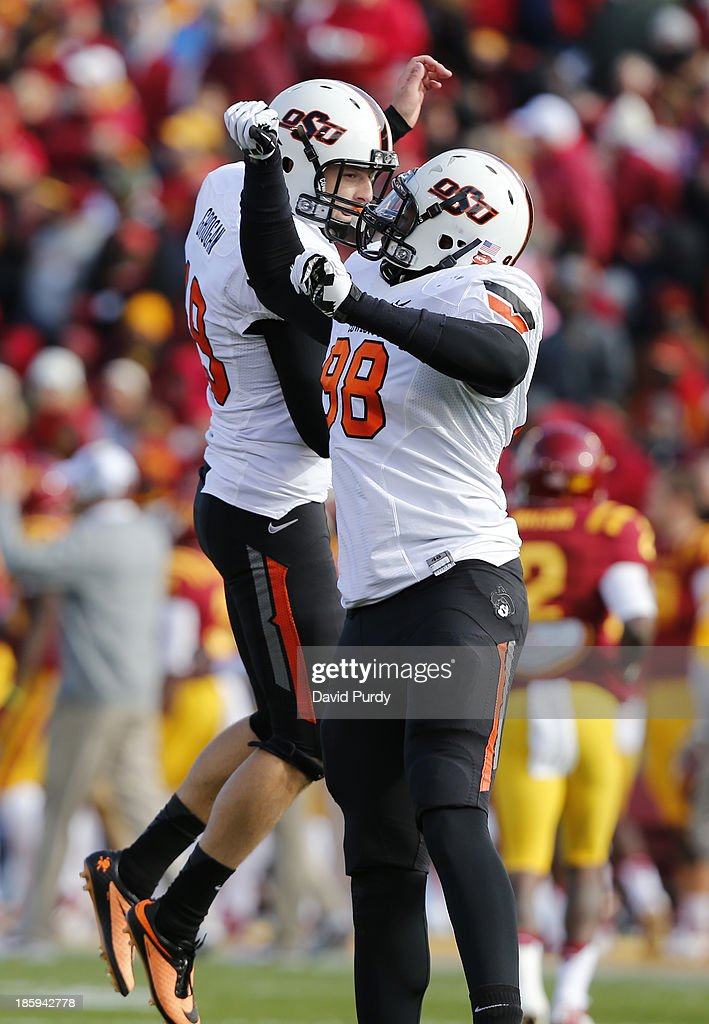 Kicker Ben Grogan #19 of the Oklahoma State Cowboys celebrates with teammate defensive tackle Davidell Collins #98 of the Oklahoma State Cowboys after kicking a field goal in the first half of play against the Iowa State Cyclones at Jack Trice Stadium on October 26, 2013 in Ames, Iowa.
