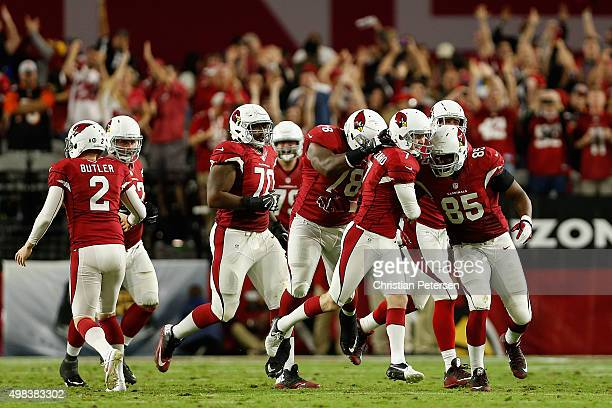 Kicker Chandler Catanzaro of the Arizona Cardinals is congratulated by Earl Watford and Darren Fells after Catanzaro kicked the game winning field...