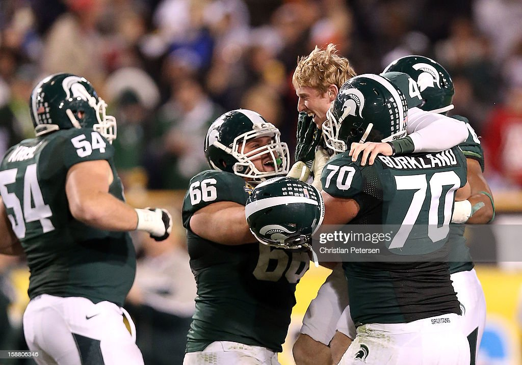 Kicker Dan Conroy #4 of the Michigan State Spartans celebrates with offensive linesman Jack Allen #66 and offensive tackle Skyler Burkland #70 after kicking a 47 yard field goal against the TCU Horned Frogs during the Buffalo Wild Wings Bowl at Sun Devil Stadium on December 29, 2012 in Tempe, Arizona. The Spartans defeated the Horned Frogs 17-16.