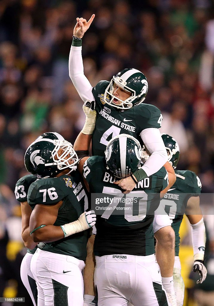 Kicker Dan Conroy #4 of the Michigan State Spartans celebrates with guard Donavon Clark #76 and offensive tackle Skyler Burkland #70 after kicking a 47 yard field goal against the TCU Horned Frogs during the Buffalo Wild Wings Bowl at Sun Devil Stadium on December 29, 2012 in Tempe, Arizona. The Spartans defeated the Horned Frogs 17-16.