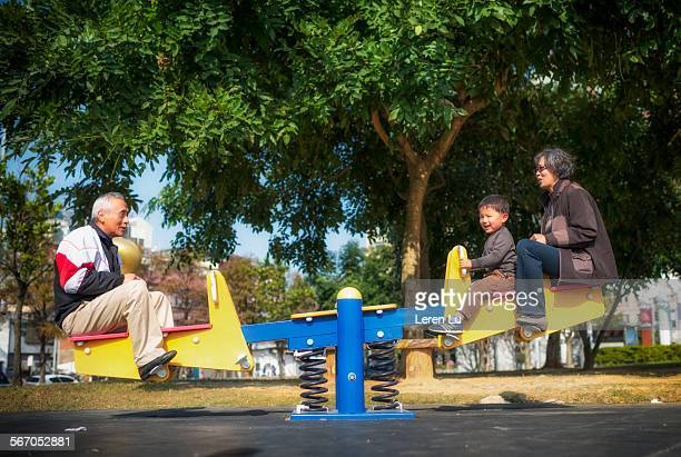Kid and grandparents playing seesaw