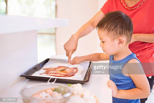 Kid and mother making pizza at home