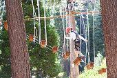 active brave boy enjoying climbing at treetop adventure park