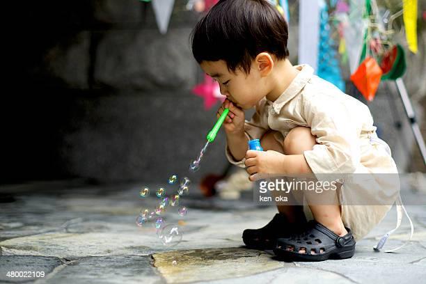 A kid blows soap bubbles