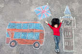 Happy little kid boy in british queen's guard soldier uniform having fun with London picture drawing with colorful chalks. With Big Ben, Union Jack and red bus.