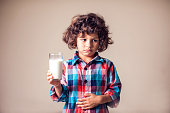 Kid boy with stomach pain holding a glass of milk. Dairy Intolerant person. Lactose intolerance, health care concept.