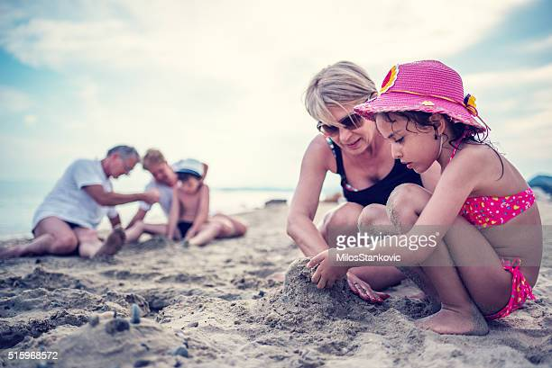 Kid building a sandcastle with grandmother at the beach