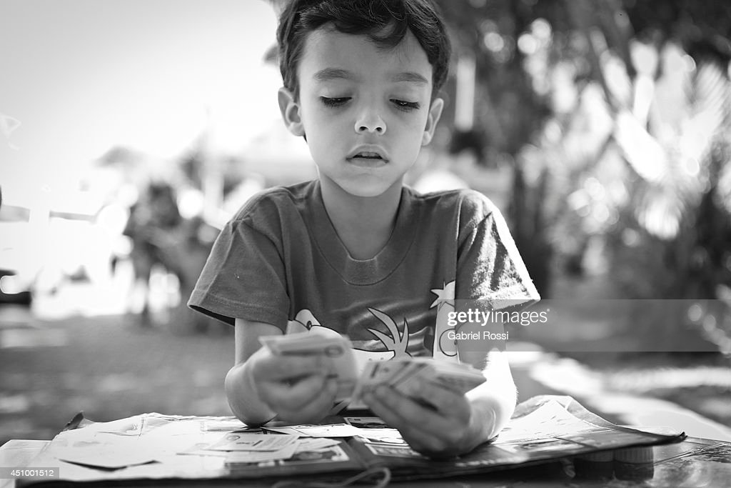 A Kid checks his duplicated Panini 2014 FIFA World Cup Brazil stickers at Praça Popular on June 21, 2014 in Cuiaba, Brazil.