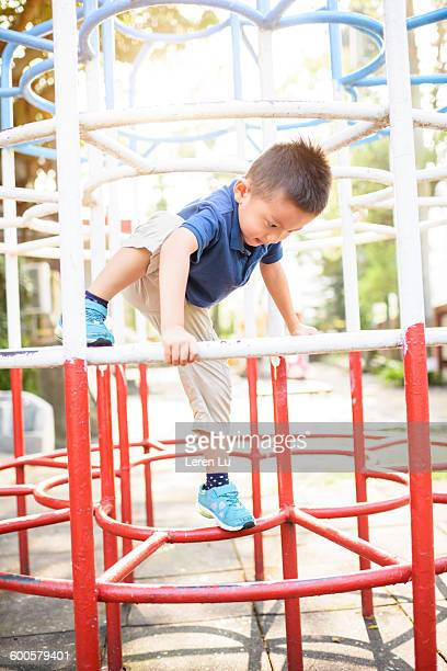 Kid climbing playground facility at park