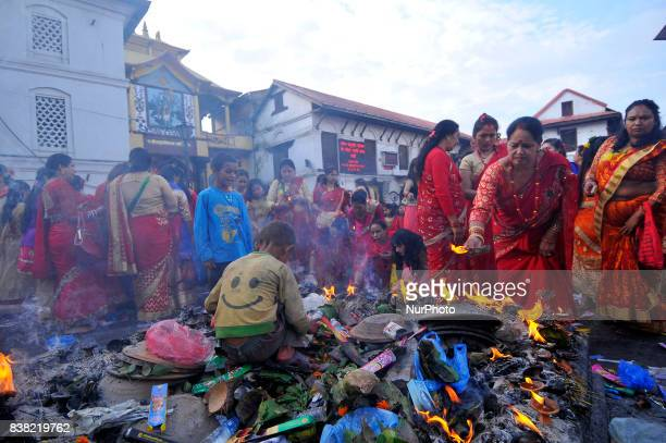 A kid collecting money as Nepalese devotees offering oil and butter lamps during Teej festival celebrations at Pashupatinath Temple Kathmandu Nepal...