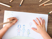 Kid drawing on white paper her happy family. Top view
