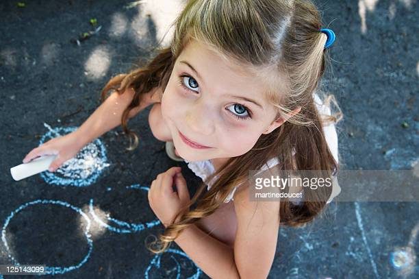 Kid drawing on the pavement of a driveway.