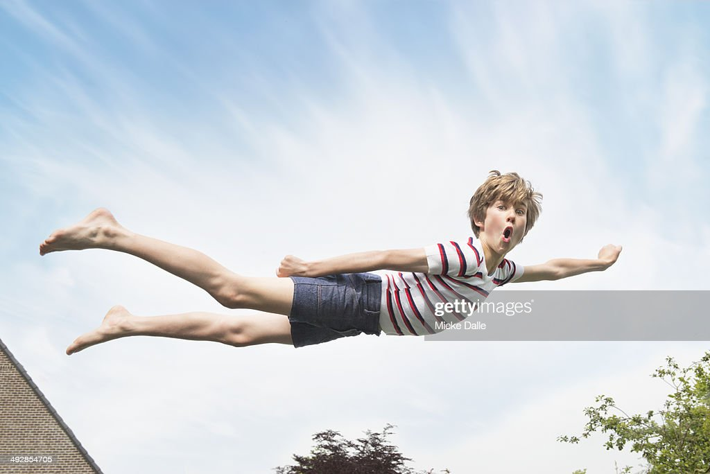 Kid flying through the air like superman : Stock Photo
