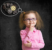 kid in glasses with bright idea standing near school blackboard in classroom