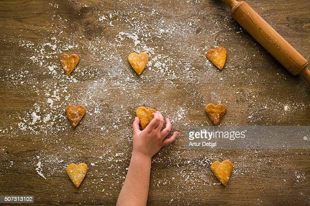 Kid grabbing a heart shaped cookie from woody table in the kitchen in view from above.
