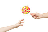 Kid reaching for big colorful lollipop in mothers hand, isolated on white background