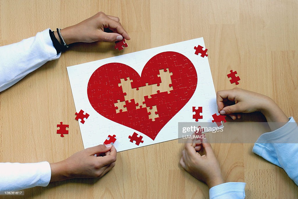 4 kid hands on a heartpuzzle : Stock Photo