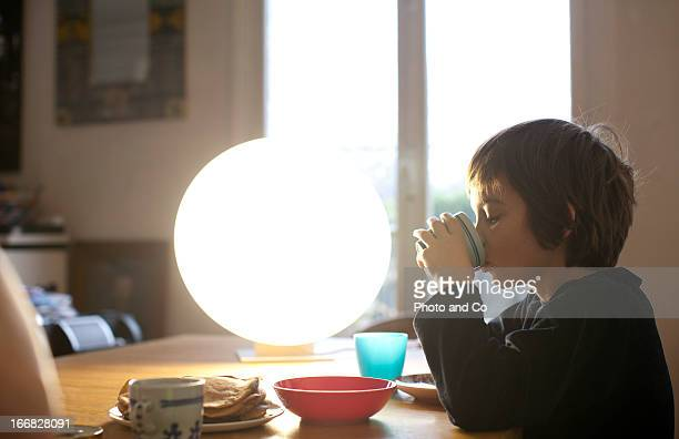 kid having breakfast with light therapy lamp