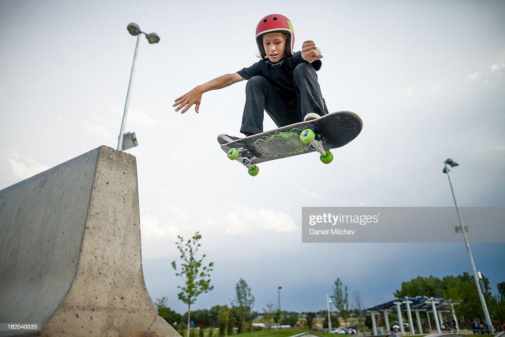 Kid, having fun skateboardin and jumping.