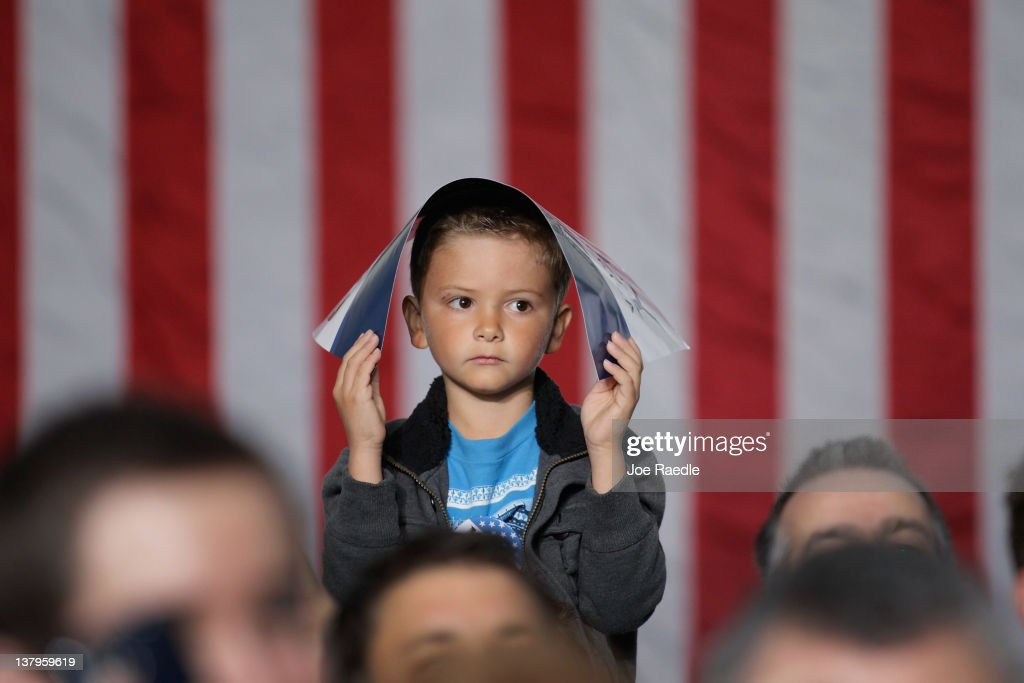 A kid holds a sign over his head as Republican presidential candidate and former Massachusetts Gov. <a gi-track='captionPersonalityLinkClicked' href=/galleries/search?phrase=Mitt+Romney&family=editorial&specificpeople=207106 ng-click='$event.stopPropagation()'>Mitt Romney</a> speaks during a rally with supporters at the Ring Power Lift Trucks January 30, 2012 in Jacksonville, Florida. Romney is campaigning across the state ahead of the January 31 Florida primary.