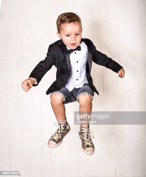 Kid in suit and bow tie jumping