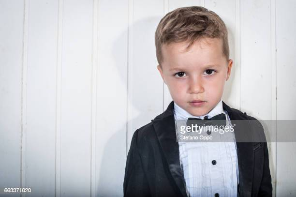 Kid in suit and bow tie looking at camera