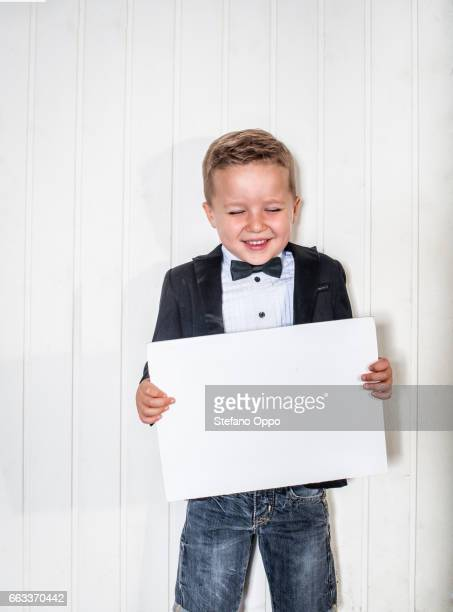 Kid in suit and bow tie with sign