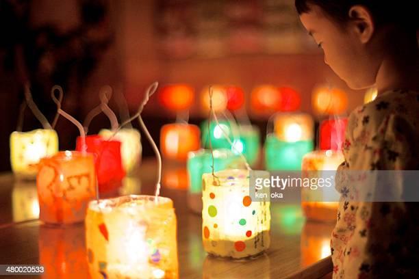 A kid is gazing at many handmade lanterns