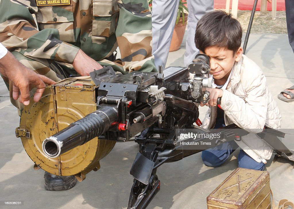 A kid is looking through a multiple grenade launcher during 'Army Equipment Display and Military Tattoo' at Army Polo Ground, Race Course on February 2, 2013 in Kolkata, India.