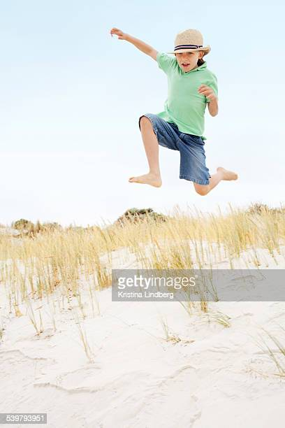 Kid jumping off sand dune facing camera