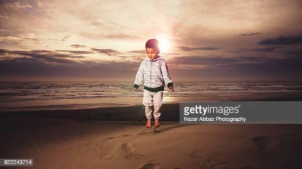 Kid Jumping on sand.